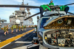 150317-N-FB203-285 PACIFIC OCEAN (March 17, 2015) Sailors from the Blackjacks of Helicopter Sea Combat Squadron (HSC) 21 perform maintenance on an MH-60S Sea Hawk helicopter on the flight deck of the Wasp-class amphibious assault ship USS Essex (LHD 2). Essex is underway participating in a composite training unit exercise with the Essex Amphibious Ready Group. (U.S. Navy photo by Mass Communication Specialist 2nd Class Sean P. Gallagher/Released)